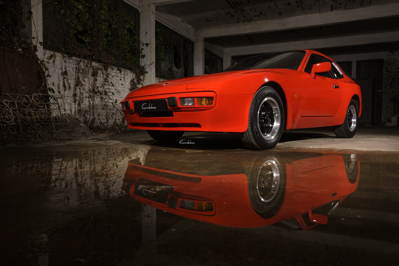 Photo de Porsche 944 rouge, dans un hangar abandonné, avec reflet de la voiture dans une flaque d'eau