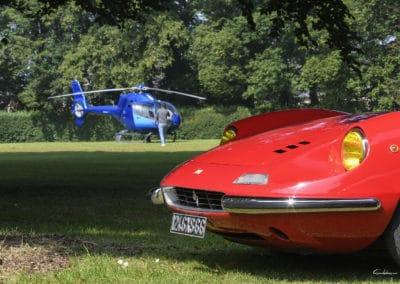 capot avant de Ferrari Dino, photographiée en 3/4 avant dans un parc lumineux, devant un hélicoptère colibri EC120
