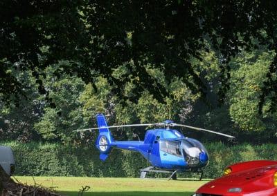 propriétaire ferrari dino allongé sous un arbre devant sa voiture et un helico EC 120 colibri