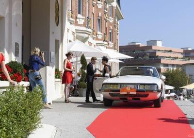 Portier aidant à sortir la passagère d'une Citroën SM cabriolet sur le perron de l'hôtel Westminster lors du concours d'élégance du Touquet Paris Plage