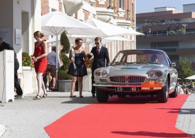 Portier aidant à sortir la passagère d'une Maserati Frua Mexico sur le perron de l'hôtel Westminster lors du concours d'élégance du Touquet Paris Plage