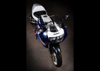 photo de Suzuki GSXR 750 SRAD blanche et bleue de 1999 sur fond noir